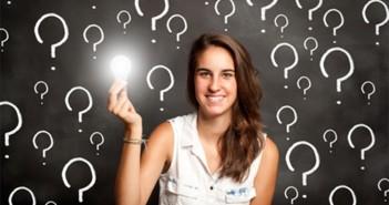 ImprendiNews – L'idea – Ragazza con una lampadina in mano simboleggiante l'idea in mezzo a tanti punti interrogativi