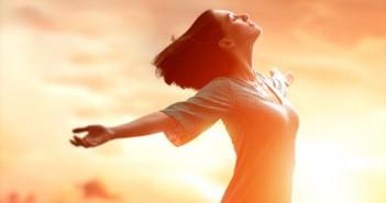 ImprendiNews – Felicità, ragazza felice con le braccia aperte che volge lo sguardo al sole